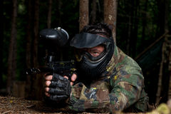 Sniper Aiming Gun. Paintball sport player in protective uniform and mask aiming and shooting with gun outdoors royalty free stock photography
