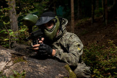Sniper Aiming Gun. Paintball sport player in protective uniform and mask aiming and shooting with gun outdoors stock images