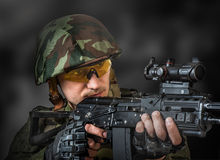 Sniper aiming a machine gun. Young handsome soldier (sniper) aiming a machine gun Stock Photos