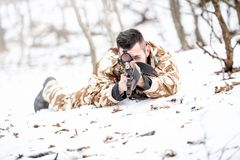 Sniper aiming through scope and shooting with rifle during operation - war concept or hunting concept Royalty Free Stock Images