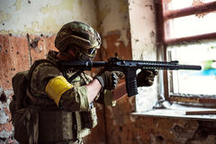 Sniper with automatic rifle by the window in building. Military man sniper with automatic rifle with a  by the window in building Stock Photo