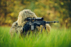 Sniper in camouflage suit looking at the target. Sniper in the grass looking through the scope Royalty Free Stock Photography