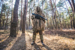 Sniper in camouflaged ghillie suit. Standing in forest with rifle in hands.Low angle view.Selective focus Stock Photo