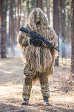 Sniper in camouflaged suit with rifle. Soldier in camouflaged sniper suit  standing in forest with rifle in hands.Selective focus Stock Image