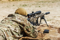 Sniper in the desert. Young male sniper in camouflage with gun in the desert Royalty Free Stock Image