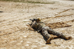 Sniper in the desert. Young male sniper in camouflage with gun in the desert Royalty Free Stock Photography