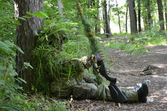 Sniper in the forest. Near the tree, camp Royalty Free Stock Photos