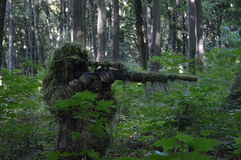 Sniper in the forest. Wearing 3d ghillie suit Royalty Free Stock Image