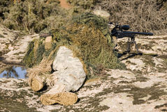 Sniper ghillie dressed pointing with sniper rifle L96-A1 - 1 Royalty Free Stock Photography