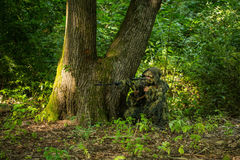 Sniper in ghillie suit. Sniper soldier man in military ghillie suit camouflage with rifle in hands aiming target sitting in ambuscade near tree in forest Stock Photos