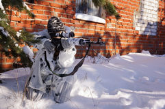 Sniper girl. In white camouflage aiming with rifle at winter forest Stock Photography