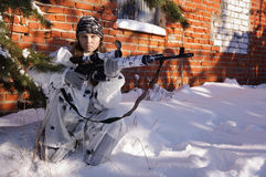 Sniper girl. In white camouflage aiming with rifle at winter forest Royalty Free Stock Photography