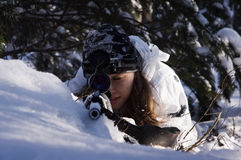 Sniper girl. In white camouflage aiming with rifle at winter forest Stock Images