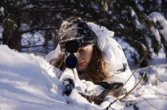 Sniper girl. In white camouflage aiming with rifle at winter forest Royalty Free Stock Photo