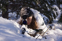 Sniper girl. In white camouflage aiming with rifle at winter forest Royalty Free Stock Photos