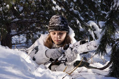 Sniper girl. In white camouflage aiming with rifle at winter forest Stock Photos
