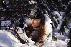 Sniper girl. In white camouflage aiming with rifle at winter forest Stock Photo