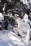 Sniper girl. In white camouflage aiming with rifle at winter forest Stock Image