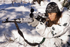 Sniper girl. In white camouflage aiming with rifle at winter forest Royalty Free Stock Image