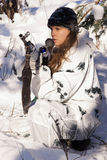 Sniper girl. In white camouflage aiming with rifle at winter forest Royalty Free Stock Images