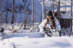 Sniper girl in white camouflage at winter forest. Sniper girl in white camouflage aiming with rifle at winter forest Royalty Free Stock Images