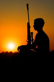The sniper has a rest. Rest of the sniper with a rifle against the coming sun Royalty Free Stock Images