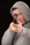 Sniper in hood aims at rifle Royalty Free Stock Image