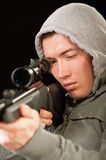 Sniper in hood aims at rifle Royalty Free Stock Photo