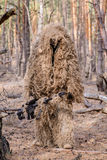 Sniper with large-caliber rifle in forest. Sniper in special camouflage suit with large-caliber rifle in forest Royalty Free Stock Photography