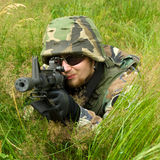 Sniper laying in a grass. A camouflaged military sniper laying in a long grass with a machine gun and aiming. ASG battle. Focus on the soldier's face Royalty Free Stock Photos