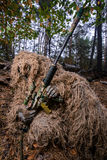 Sniper reload his rifle in forest. Camouflaged sniper in forest reload his rifle with scope royalty free stock images