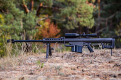 Sniper rifle Barrett M82. Forest background Royalty Free Stock Photography