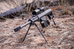 Sniper rifle on bipod with scope on ground background Royalty Free Stock Photos