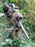 Sniper Rifle in Grass. A .308 caliber bolt rifle with some partial camouflage Royalty Free Stock Photo