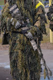 Sniper rifle. In hands of sniper in camouflage ghillie suit Royalty Free Stock Images
