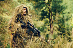 Sniper soldier stands with arms and looking at the target Royalty Free Stock Images