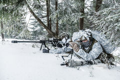 Sniper and spotter somewhere above the Arctic circle. Winter arctic mountains warfare. Action in cold conditions. Sniper and spotter with weapons in wait Royalty Free Stock Images
