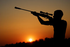 The sniper for a sunset. The man who shoots from a sniper rifle against a sunset Stock Photos