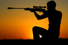The sniper for a sunset. The man who shoots from a sniper rifle against a sunset Royalty Free Stock Image