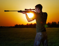 Sniper for a sunset. The young man with a sniper rifle aims against a decline Royalty Free Stock Photography
