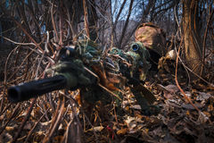 Sniper wearing camouflage suit with rifle hide in the woods Stock Images