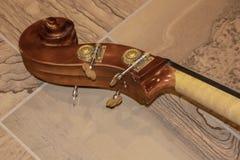 Snirkeln av en violoncell som komponeras av mutterpegbox och pinnecloseupen som ligger på tegelplattagolvet - selektiv fokus royaltyfri bild