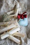 Snirklar för inbjudan för brölloptappningpapper och blå keramisk hjärta med den röda pilbågen på en säckväv Arkivbild
