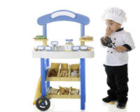 Snitching Baker. A preschool baker-chef snitching cookies from his vending stand.  Signs on the stand are left blank for your text.  On a white background Stock Photos