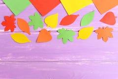 Snitt för höstsidor från kulört papper Röda, gröna och apelsinpapperssidor för guling, på blå träbakgrund med tomt utrymme Royaltyfria Bilder