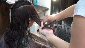 Snitt för för kvinnafrisörhårkammar och sax håret av en flicka som sitter framme av en spegel i skönhetsalongen N?rbild stock video