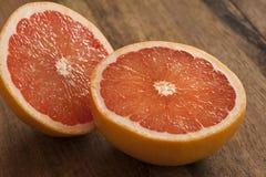 Snitt för rosa grapefrukt i halva på trätabellen Arkivfoto