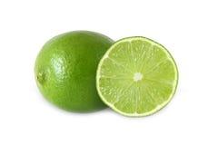 Snitt och hela limefruktfrukter som isoleras på vit bakgrund Arkivfoto