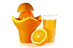 Snittapelsinen på en fruktsaftutsugningsfläkt och ett fruktsaftexponeringsglas Royaltyfria Foton