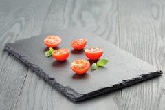 Snittet i halva körsbärsröda tomater kritiserar på brädet arkivfoton